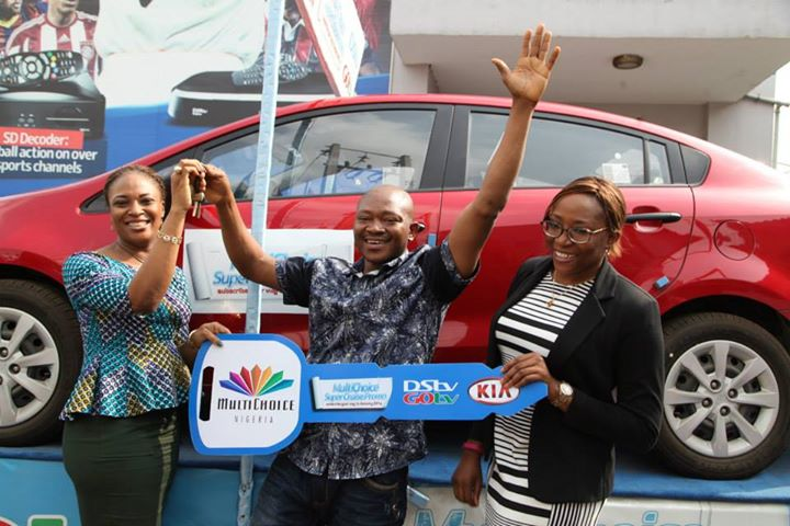 L-R: Chioma Afe, Marketing Manager, DStv; Winner of the brand new Kia Rio car, Ndubuisi Achazie and Caroline Oghuma, Public Relations Manager, DStv during the MultiChoice Super Cruise Promo Car presentation — at DStv Office Surulere Rasaq Balogun Street, Surulere, Lagos.